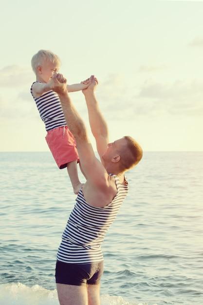 Papai está segurando o filho nas mãos estendidas no litoral. diverta-se Foto Premium
