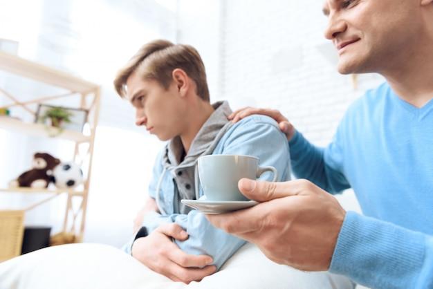 Papai estende a mão com café. Foto Premium