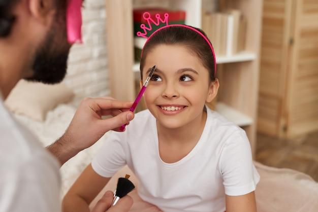 Papai limpa rosto de filhas pequenas com um pincel. Foto Premium