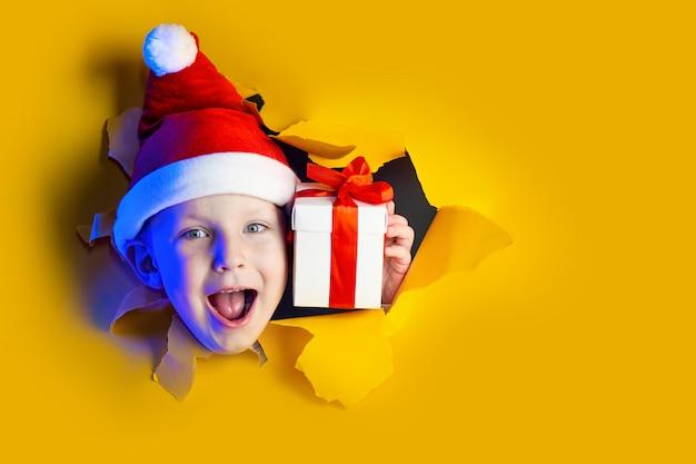 Papai noel alegre dá um presente, saindo do fundo amarelo brilhante irregular Foto Premium