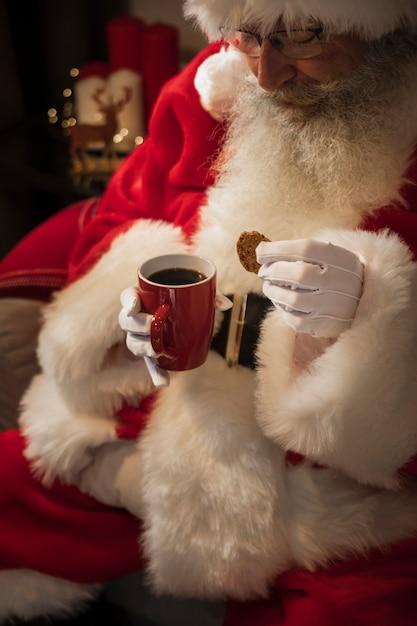 Papai noel bebendo uma xícara de café Foto gratuita