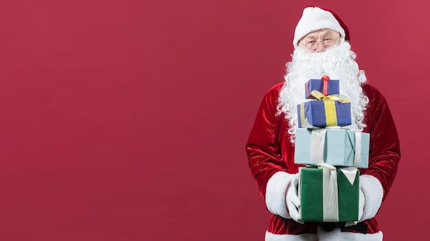 Papai noel com presentes coloridos nas mãos Foto gratuita