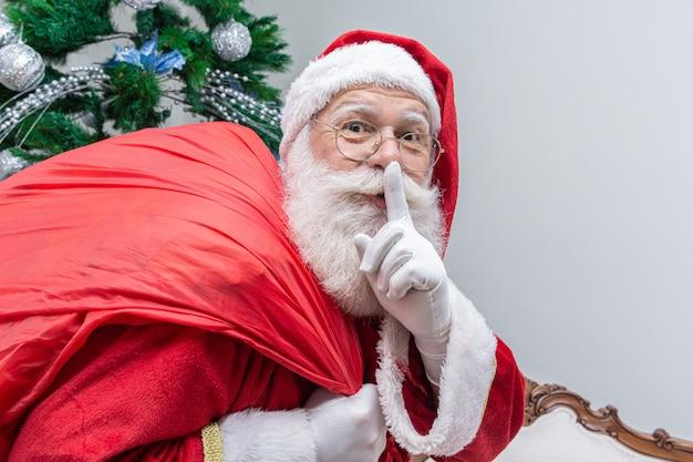 Papai noel com saco vermelho, mantendo o dedo indicador pela boca e olhando para a câmera Foto Premium