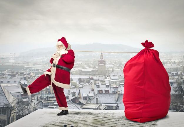 Papai noel com um pacote grande em um telhado Foto Premium