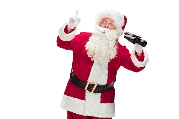 Papai noel com uma barba branca luxuosa, chapéu de papai noel e um traje vermelho isolado em um fundo branco com binóculos Foto gratuita