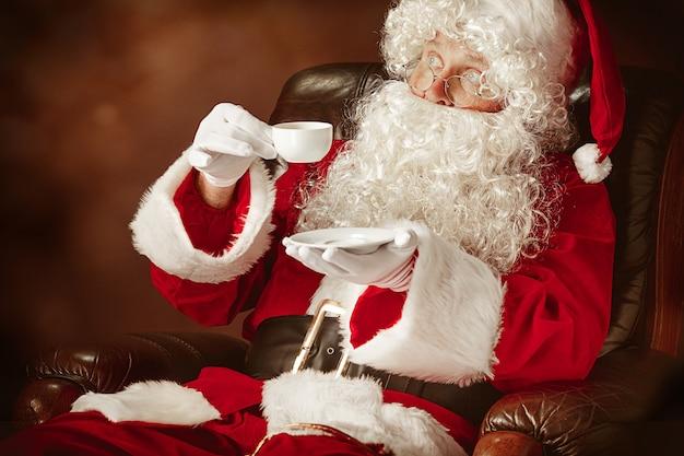 Papai noel com uma luxuosa barba branca, chapéu de papai noel e uma fantasia vermelha sentado em uma cadeira com uma xícara de café Foto gratuita