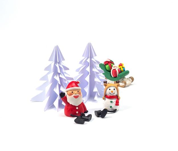 Papai noel e homem da neve sentaram-se em frente à árvore de natal de origami, com o trenó cheio de detalhes esperando o festival da felicidade Foto Premium