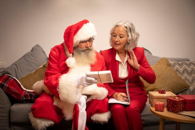 Papai noel e mulher preparando presentes de natal Foto gratuita