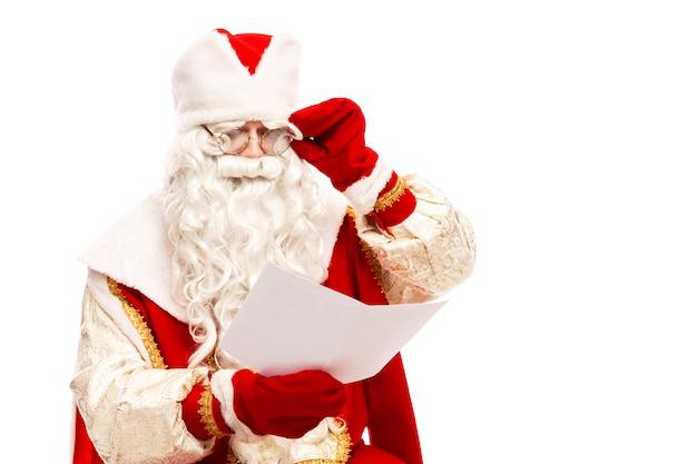 Papai noel em copos lendo uma carta de desejo com uma lista de presentes. isolado em um fundo branco. Foto Premium