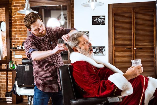 Papai noel fazendo a barba de seu barbeiro pessoal Foto gratuita