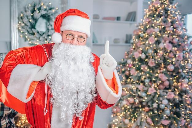 Papai noel maduro se levanta e aponta para cima. ele olha com uma visão séria. há uma árvore de natal atrás dele. Foto Premium