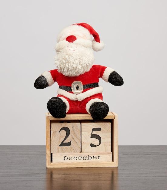 Papai noel no chapéu vermelho, calendário de mesa de madeira com a data 25 de dezembro Foto Premium