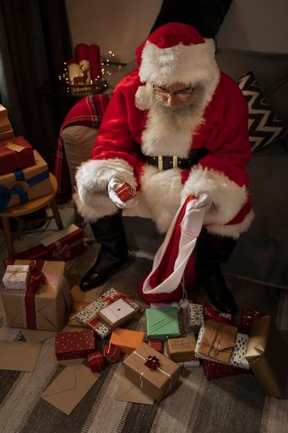 Papai noel preparando seu saco de presentes Foto gratuita