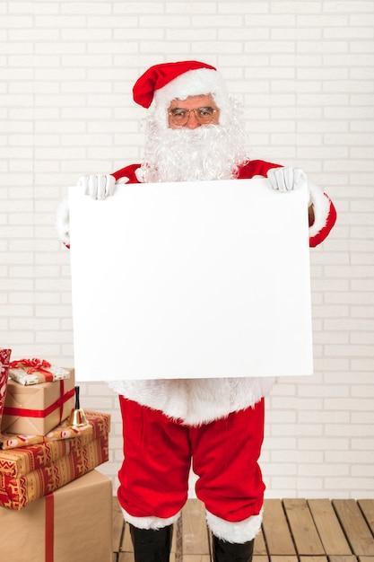 Papai noel segurando cartaz branco em branco Foto gratuita