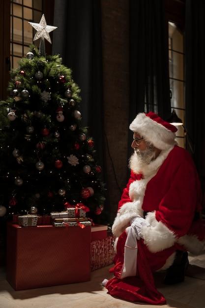 Papai noel sentado ao lado da árvore de natal Foto gratuita