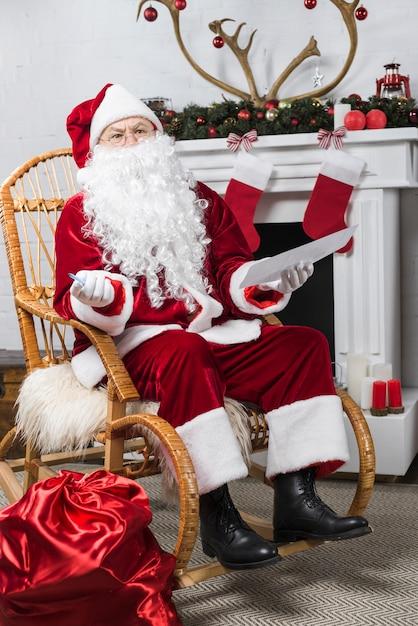 Papai noel sentado na cadeira de balanço com wishlist Foto gratuita