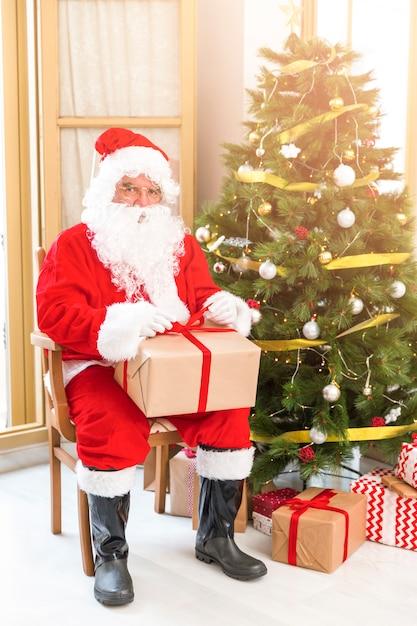 Papai noel sentado perto da árvore de natal com presente Foto gratuita