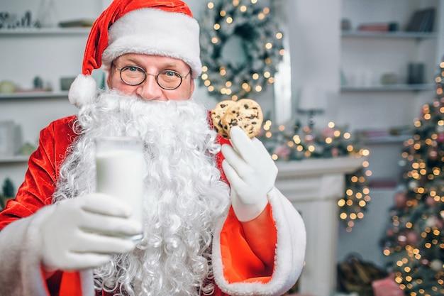 Papai noel tem copo de leite e dois biscoitos nas mãos. ele oferece. Foto Premium