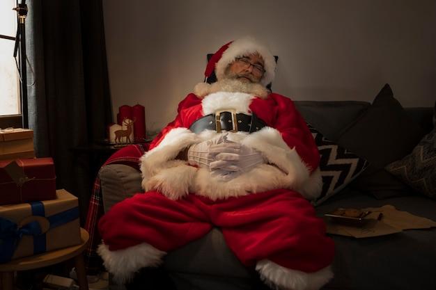 Papai noel tirando uma soneca no sofá Foto gratuita