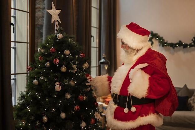 Papai noel tocando a árvore de natal Foto gratuita