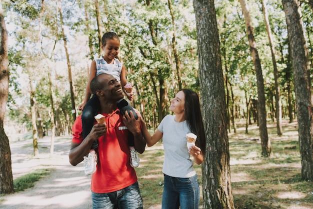 Papai rola uma garotinha em volta do pescoço na floresta. Foto Premium