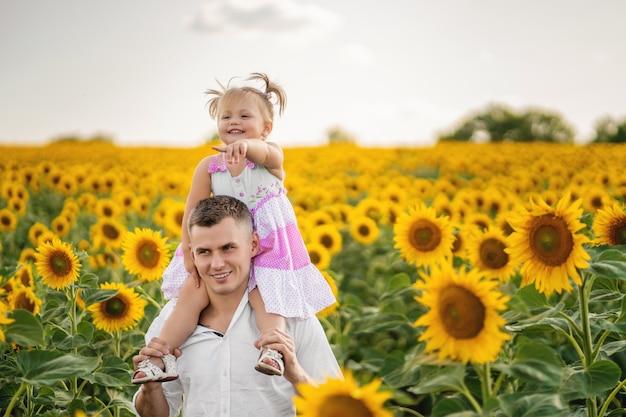 Papai segura nos ombros uma filhinha. a garota aponta para algo com o dedo. campo de girassol. pôr do sol Foto Premium