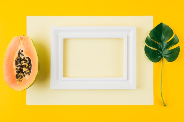 Papaia cortada ao meio; folha de monstera e moldura de madeira branca em papel contra fundo amarelo Foto gratuita