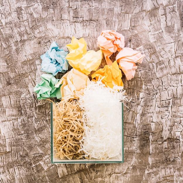 Papéis amassados sobre o recipiente de vidro preenchido com woodhave e plasticshave Foto gratuita