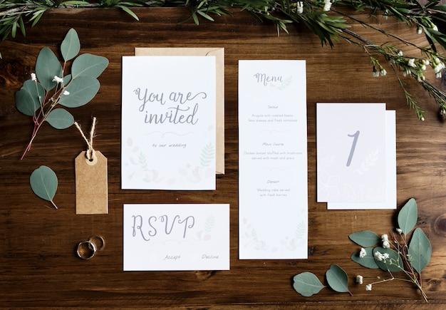 Papéis de cartões de convite de casamento deitado na mesa decorar com folhas Foto Premium