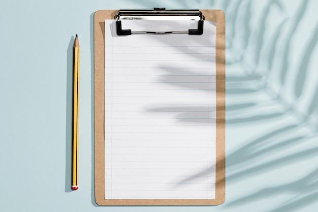 Papéis de prancheta vazio vista superior e caneta com sombras Foto gratuita