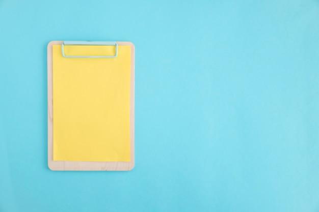 Papel amarelo na prancheta de madeira sobre o fundo azul Foto gratuita