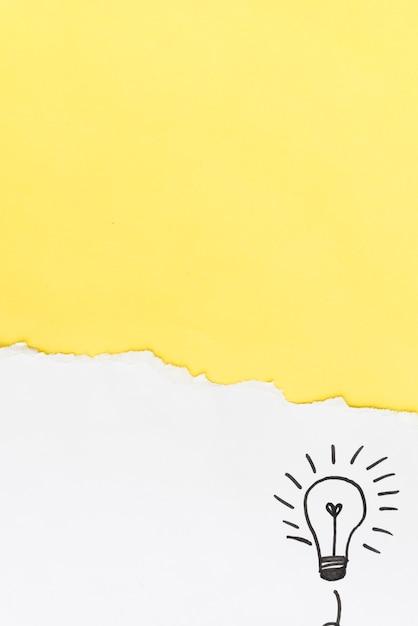 Papel amarelo rasgado com lâmpada de mão desenhada no fundo branco Foto gratuita