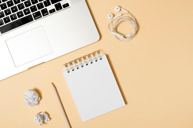 Papel amassado; bloco de anotações; lápis; fone de ouvido; e laptop sobre fundo bege Foto gratuita