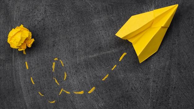 Papel amassado e avião de papel com metáfora de idéia de trilha Foto gratuita