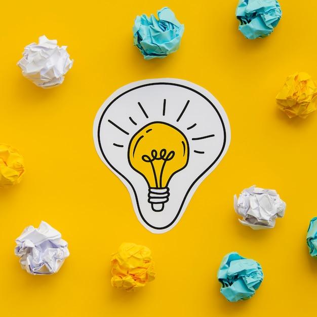 Papel amassado e desenho de uma lâmpada de ouro Foto gratuita
