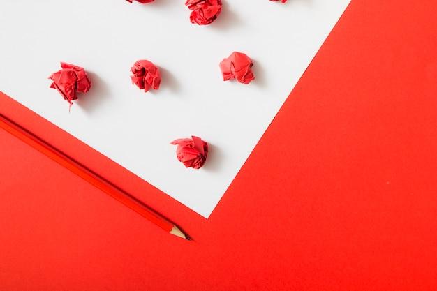 Papel amassado vermelho sobre fundo de papel duplo branco e vermelho com lápis Foto gratuita