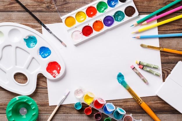 Papel, aquarelas, pincel e algumas coisas de arte na mesa de madeira Foto Premium