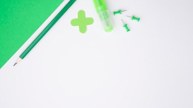Papel artesanal verde; lápis; cola e empurre o pino sobre a superfície branca Foto gratuita