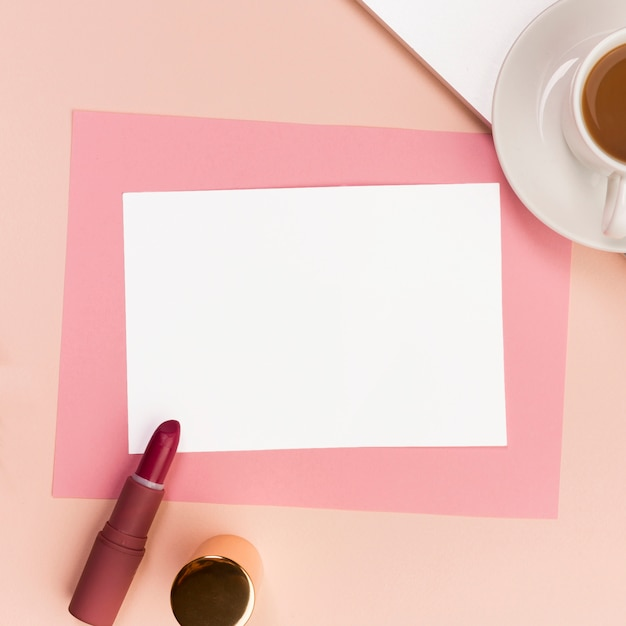 Papel branco e rosa em branco com batom, pincel de maquiagem e xícara de café Foto gratuita