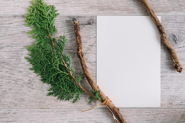 Papel branco em branco com galho de cedro e filial em plano de fundo texturizado de madeira Foto gratuita