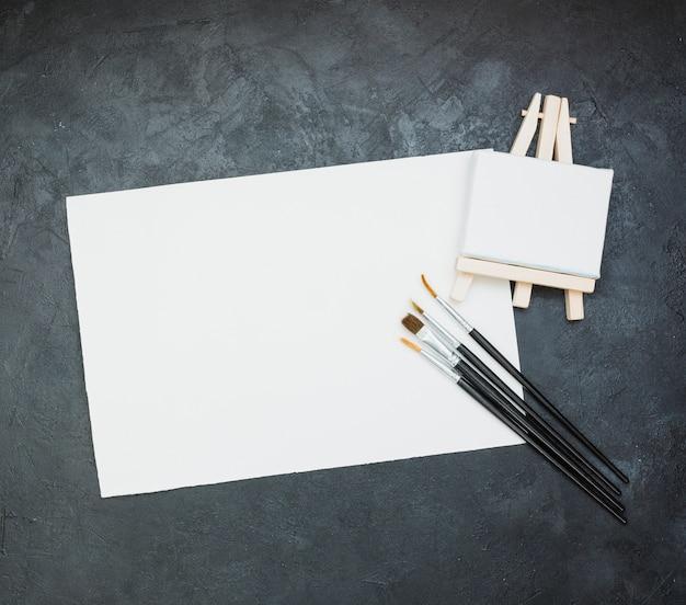 Papel branco em branco com mini cavalete e pincel em pano de fundo de ardósia Foto gratuita
