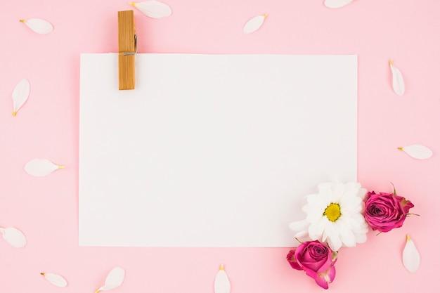 Papel branco em branco com prendedor de papel e flores sobre fundo rosa Foto gratuita