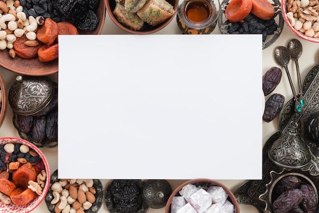 Papel branco em branco sobre os tradicionais doces e nozes para o ramadã Foto gratuita