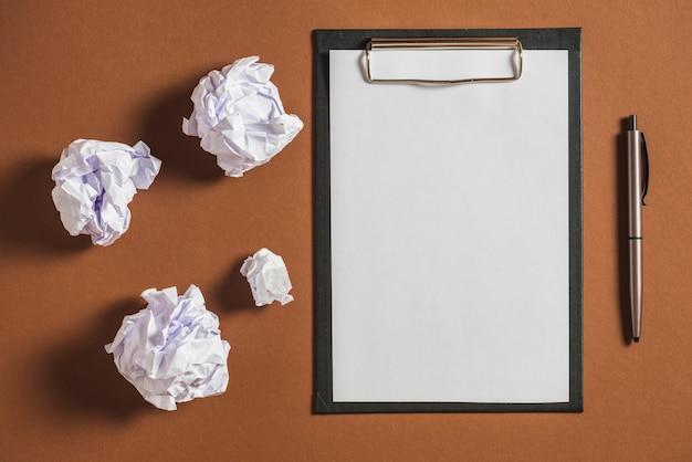 Papel colidido, caneta com papel em branco na prancheta contra um fundo colorido Foto gratuita