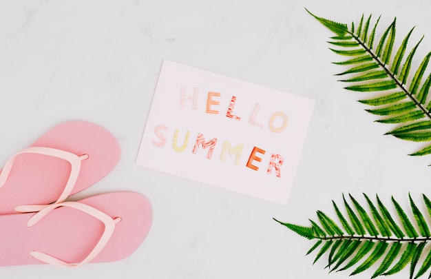 Papel com mensagem olá verão e flip-flops Foto gratuita