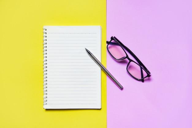 Papel de bloco de notas ou caderno com caneta e óculos rosa amarelo para o conceito de educação e negócios Foto Premium