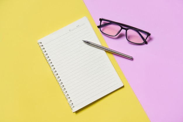 Papel de bloco de notas ou caderno com caneta e óculos rosa amarelo Foto Premium