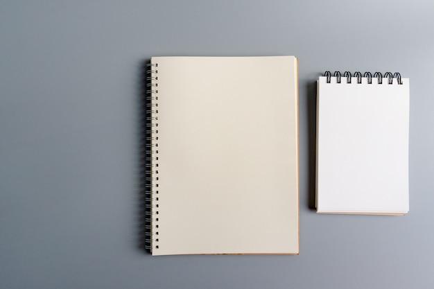 Papel de caderno aberto em branco sobre cinza, equipamento de escritório, escola estacionária e conceito de educação Foto Premium