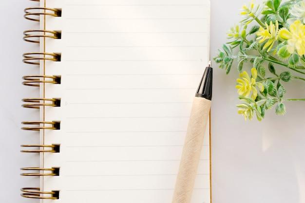 Papel de caderno em branco e caneta em fundo de mármore branco, com espaço de cópia de texto, vista superior Foto Premium