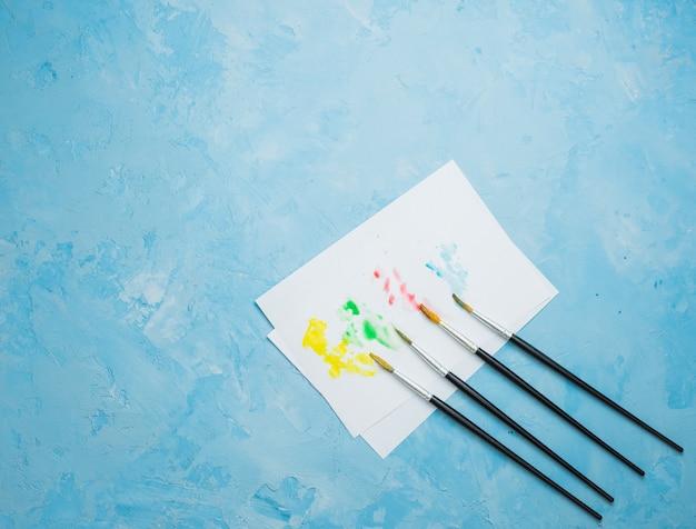 Papel de desenho colorido manchado com pincel sobre fundo azul Foto gratuita